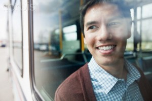 Young smiling man looking through bus window